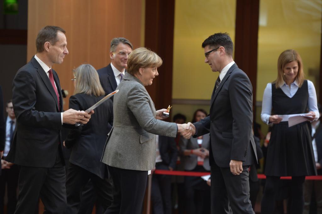 """Preisverleihung """"Sterne des Sports"""" in Gold 2015 am 26.01.2016 in der DZ Bank in Berlin. v.l.n.r. Alfons Hörmann (Präsident des Deutschen Olympischen Sportbundes), Uwe Fröhlich (Präsident Bundesverband der Deutschen Volksbanken und Raiffeisenbanken), Angela Merkel (Bundespräsidentin), Hendrik Dörr (HartfüßlerTrail e.V.), Katrin Müller-Hohenstein (Radio- und Fernsehmoderatorin)"""
